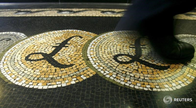 An employee is seen walking over a mosaic of pound sterling symbols set in the floor of the front hall of the Bank of England in London, in this March 25, 2008 file photograph. — Reuters pic