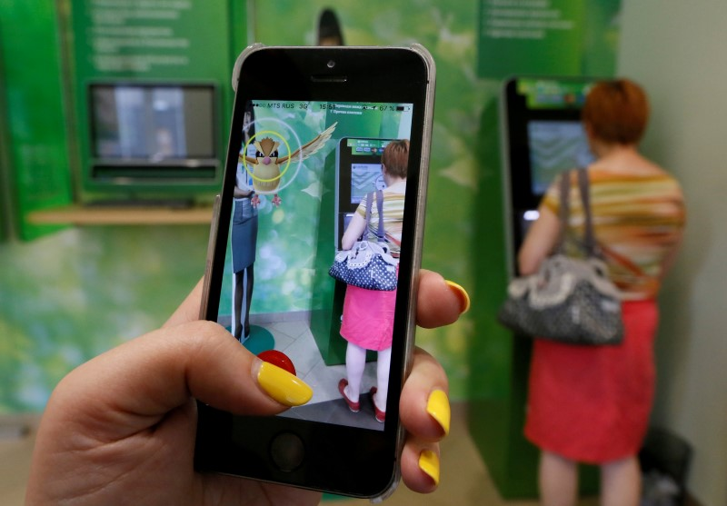 A woman plays the augmented reality mobile game 'Pokemon Go' by Nintendo, as a visitor uses an automated teller machine (ATM) at a branch of Sberbank in central Krasnoyarsk, Siberia, Russia, July 20, 2016. — Reuters pic