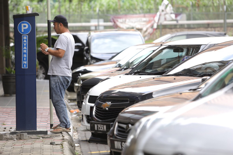 A motorist inserts money into an automated parking fees machine at Jalan Kenanga, Kuala Lumpur, July 18, 2016. DBKL has hiked parking rates to RM2 for the first hour and RM3 for the second hour with a maximum two-hour parking limit. — Picture by Choo Choy May
