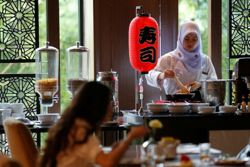 A Muslim employee cooks as a visitor has breakfast at the Al Meroz hotel in Bangkok, August 29, 2016. — Reuters pic