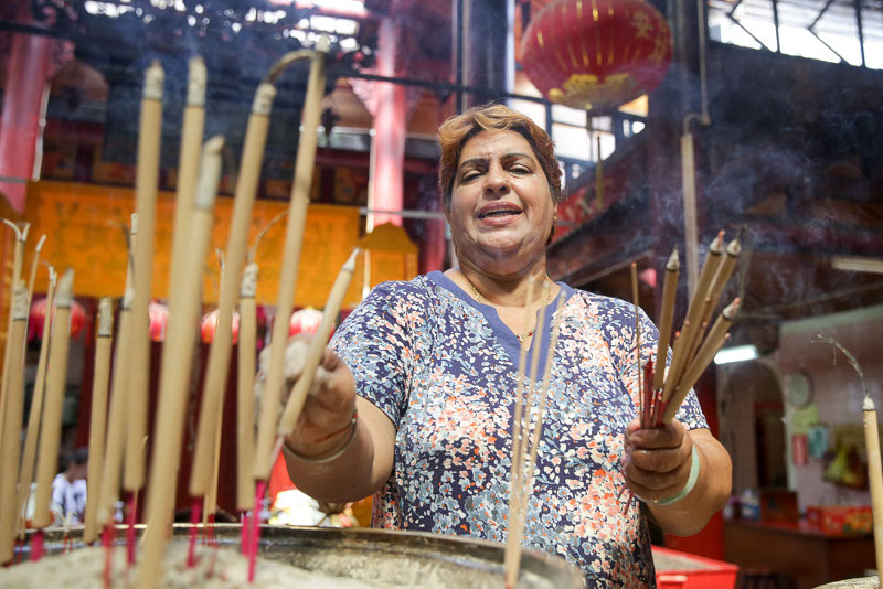 Ranjit's duties at the temple include clearing away old joss sticks placed by temple patrons
