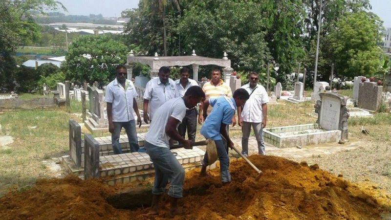 Dhatchinamoorthy and KHAIS members at a cemetery.