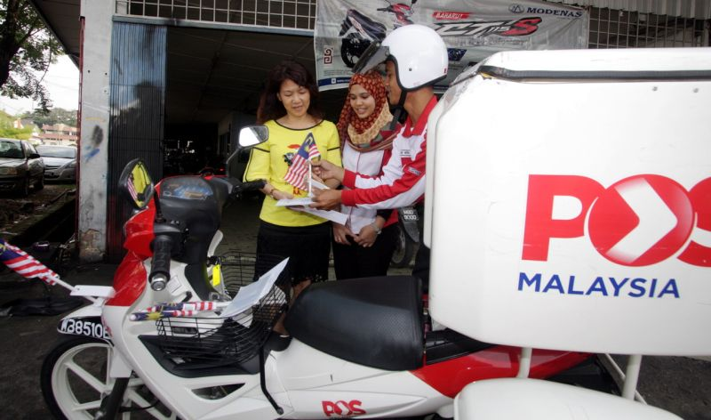 A postman hands over a letter with the Jalur Gemilang to a customer in conjunction with the Merdeka month. ― Bernama pic