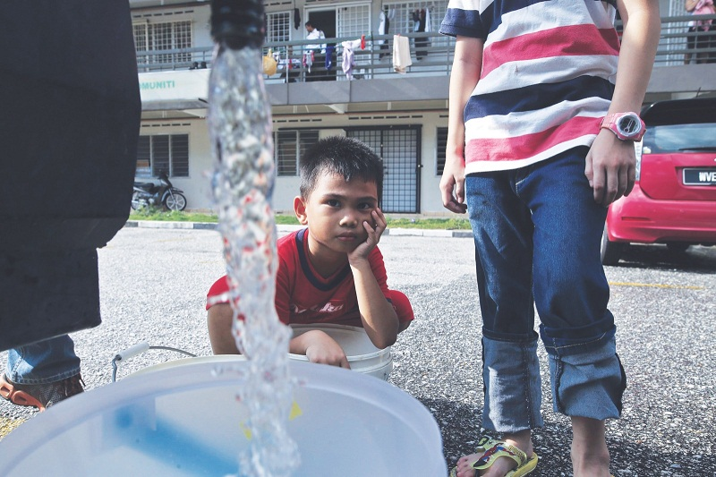 Mohd Ikmal Zafri, eight, waits anxiously for his water bucket to be filled when Syabas water tanker came to his neightbourhood in USJ 6.