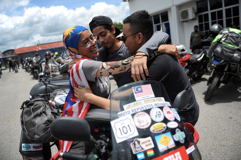 Sports science lecturer Anita Yusof (left) embracing her children after arriving at Bukit Kayu Hitam on September 16, 2016, after successfully riding a motorcycle more than 65,000km across four continents and 40 countries. — Bernama pic