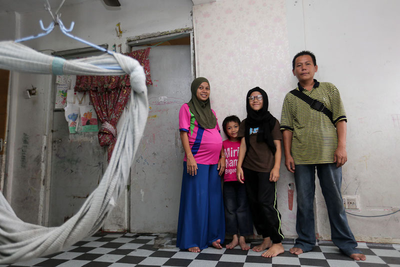 Rizal Ramli, Nor Azizah Karin and two of their seven children pose for a picture at their Kota Damansara PPR unit. — Picture by Choo Choy May