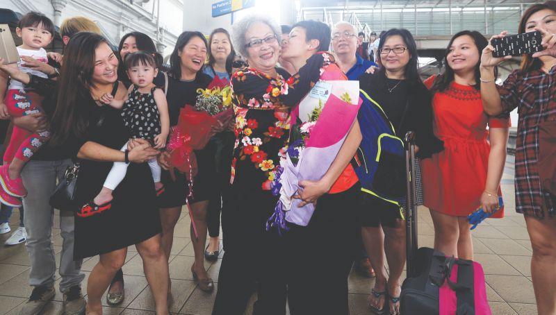 Cheong Jun Hoong kisses her grandmother Cheou Tin Goh at the Ipoh KTM train station. — Picture by Farhan Najib Yusoff
