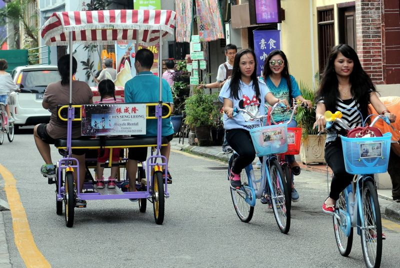 Tourists cycle along Armenian Street, situated within the core zone of the George Town's World Heritage Site, September 17, 2016. ― Bernama pic