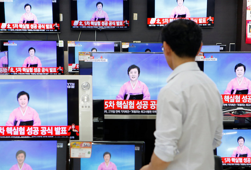 A sales assistant watches TV sets broadcasting a news report on North Korea's fifth nuclear test, in Seoul, South Korea, September 9, 2016. — Reuters pic