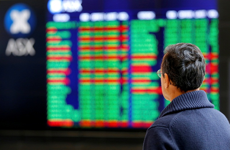 An investor looks at a board displaying stock prices at the Australian Securities Exchange (ASX) in Sydney. — Reuters file pic