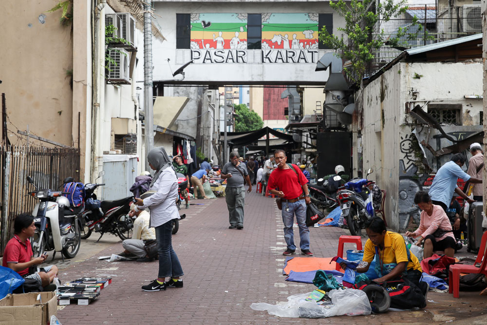 Traders selling counterfeit goods as potential customers look on.