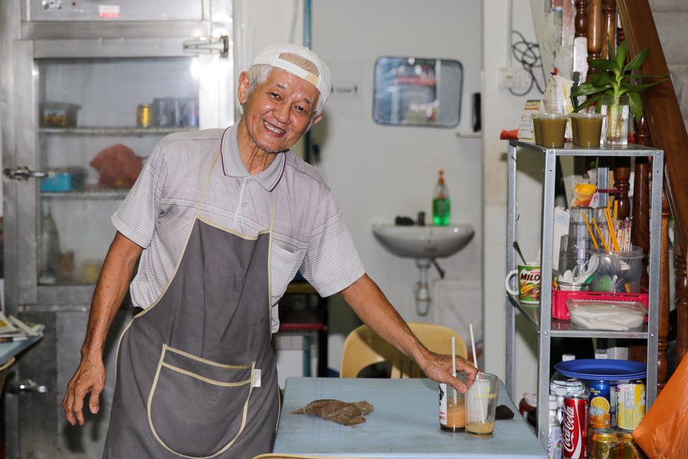Uncle Lee smiling and posing inside his tiny Onn Loke Kopitiam.