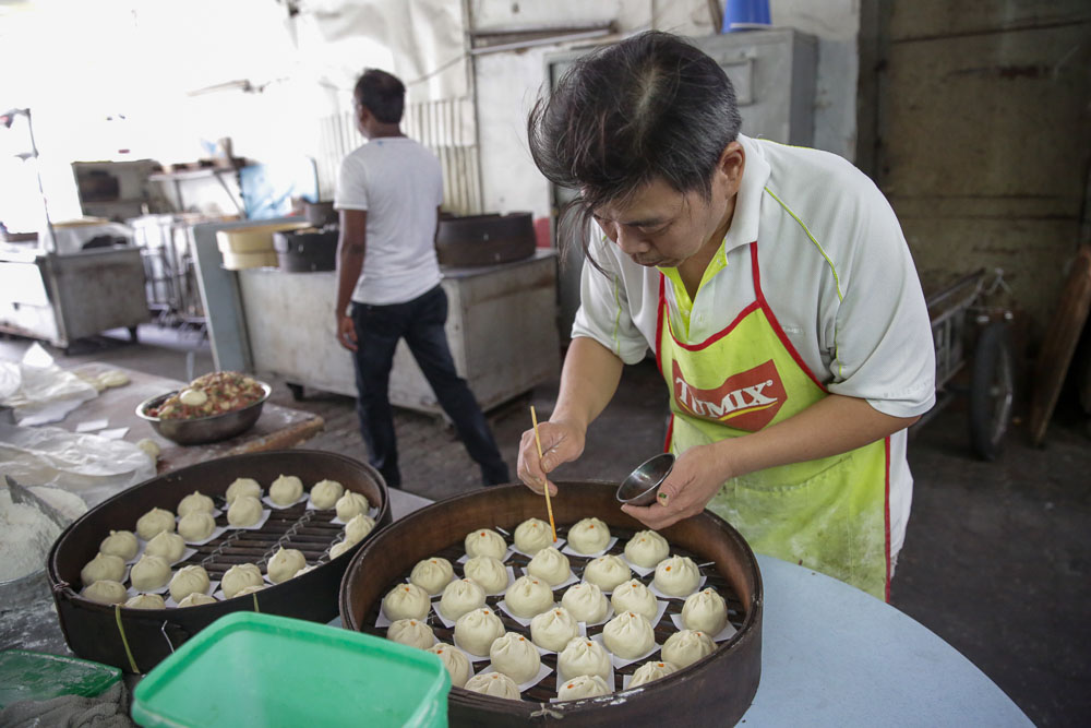 Chan Kam Weng preparing his pau (steamed bun) for customers. He makes about 300 pau in one day, all handmade to perfection.