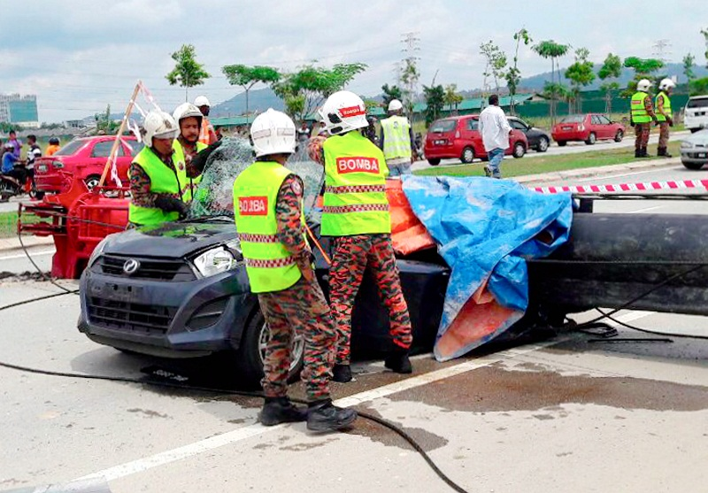 Firemen try to remove the bodies of the two victims who were crushed to death after a piledriver fell on their car in Meru, Klang November 4, 2016. — Bernama pic