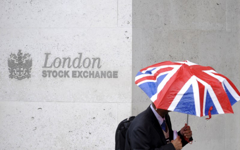 A worker shelters from the rain under a Union Flag umbrella as he passes the London Stock Exchange in London, October 1, 2008. — Reuters pic