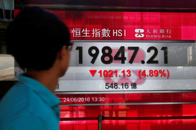 A passerby looks at a panel displaying the falling Hang Seng Index in response to British exit from the European Union, in Hong Kong June 24, 2016. — Reuters pic