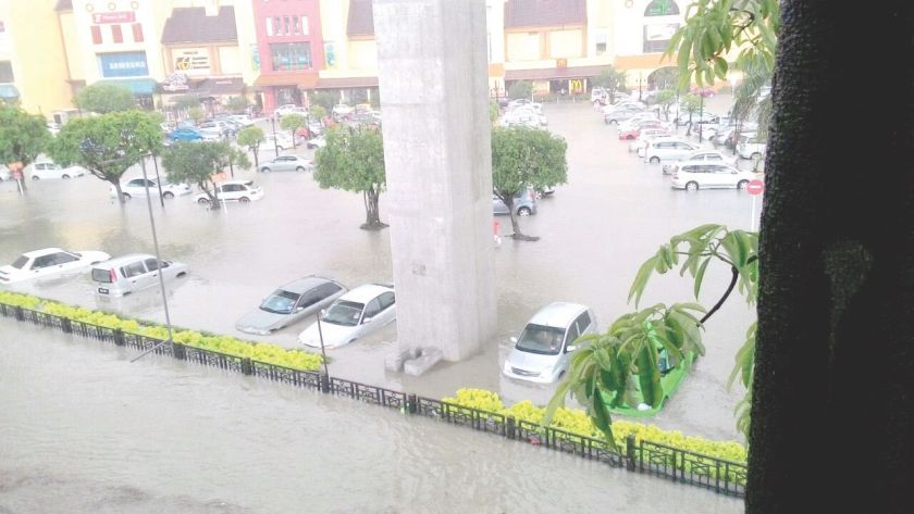 The parking lot at IOI Mall was flooded, trapping several vehicles including Nur Izzati's green Honda (left, hidden behind leaves). — Malay Mail pic