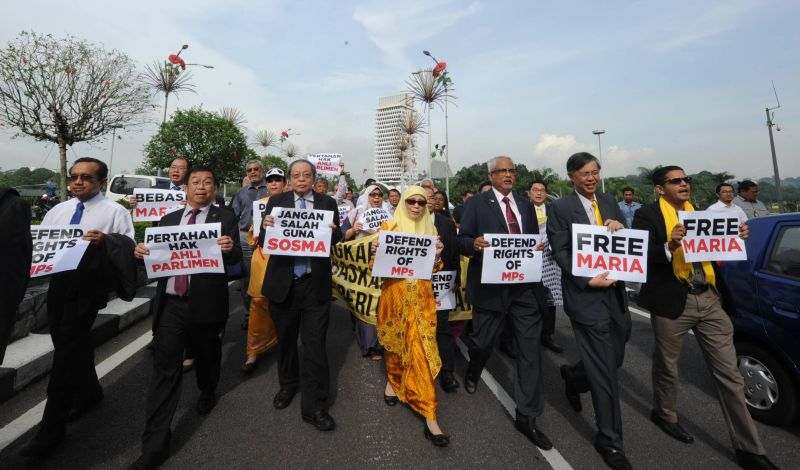 Opposition lawmakers marched to Bukit Aman while bearing placards to protest what they allege to be 'harassment' of MPs performing their duty.