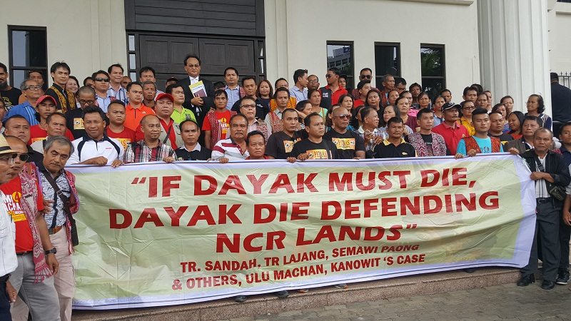 The Dayak landowners, who come from all over Sarawak, with a banner outside Kuching High Court complex, giving their support to the headman Sandah anak Tabau and seven other landowners in Kuching December 20, 2016. — Pictures by Sulok Tawie