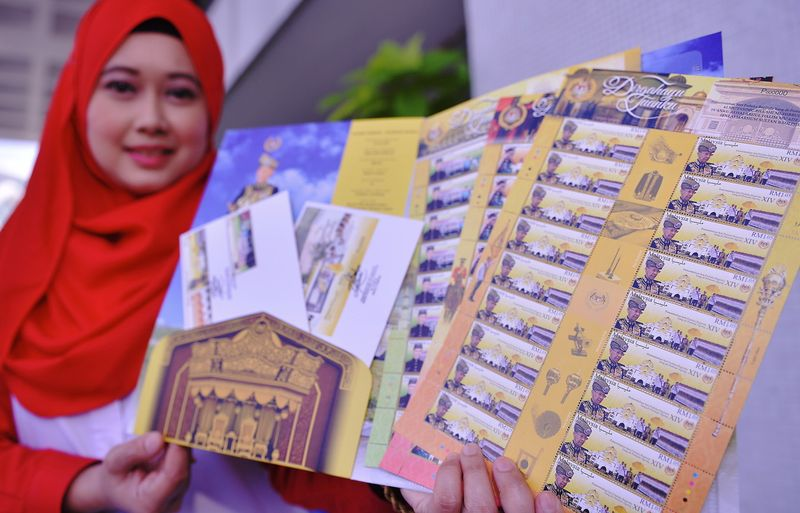 Pos Malaysia Berhad officer, Norsazila Zainuddin showing the special stamps of the Yang di-Pertuan Agong after a pre-launch press conference at Pos Malaysia headquarters, Kuala Lumpur, December 6, 2016. — Bernama pic