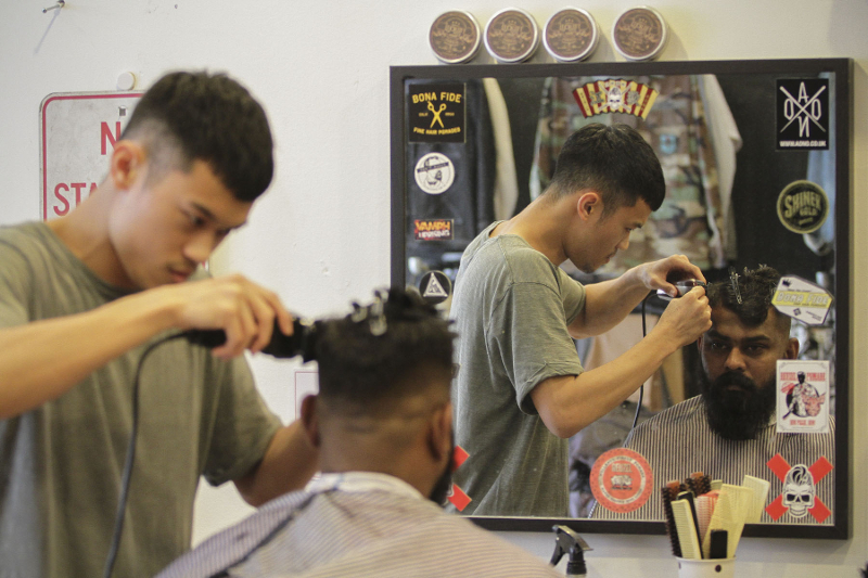 A barber at Othrs giving his client a pompadour haircut. — Picture by Yusof Mat Isa