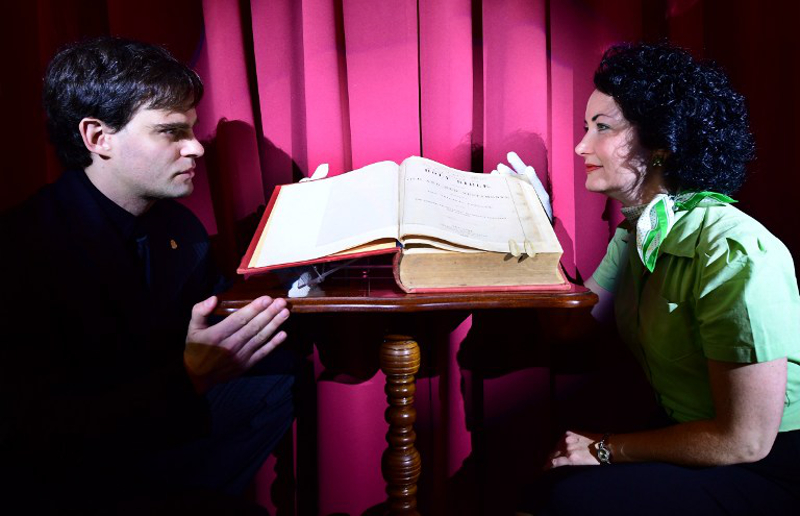 The museum's founder, Italian-Hungarian escape-artist David Merlini (left) and New York-based singer-songwriter Tara O'Grady (right) show Harry Houdini's bible in the 'House of Houdini' museum in Budapest December 3, 2016.