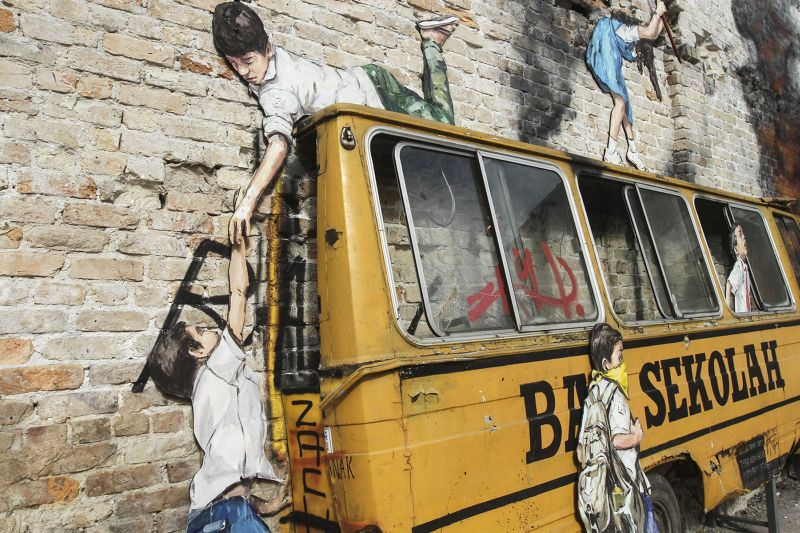 The artwork sports Zacharevic's 'Zach' signature in both black and red on the side of the schoolbus and on sliding panels of a window respectively. ― Picture by Yusof Mat Isa