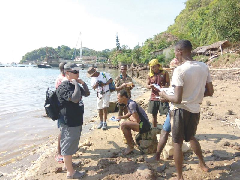 China national Bai Shuan Fu (left) and other next of kin hand out brochures to fishermen near Antsirake in Madagascar. ― Picture courtesy of Grace Nathan