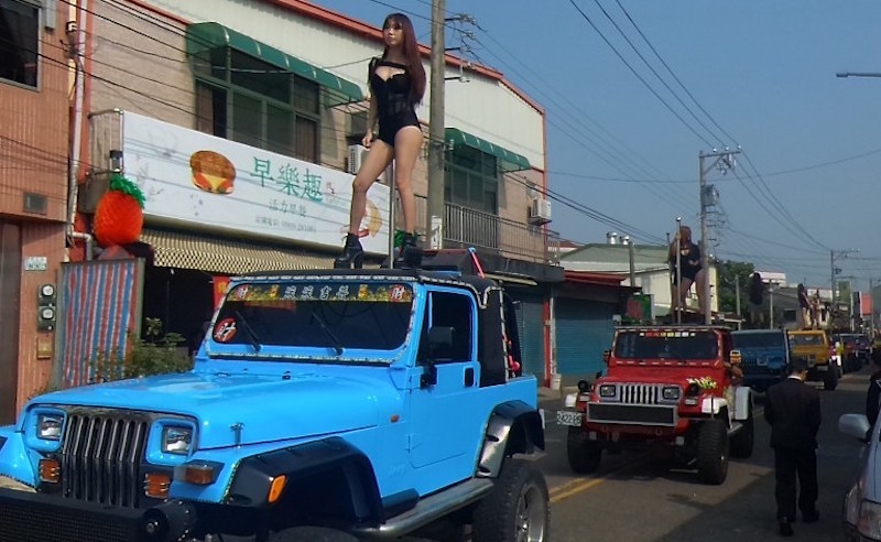 Pole dancers perform on top of jeeps during the funeral procession of former Chiayi City county council speaker Tung Hsiang in Chiayi City, southern Taiwan, January 3, 2017. — AFP pic