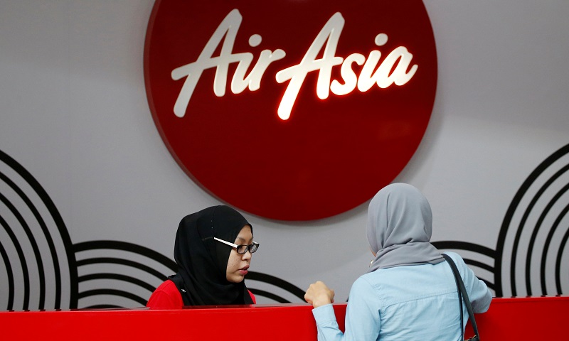 An AirAsia counter staff attends to a customer at Kuala Lumpur International Airport (KLIA) August 28, 2016. — Reuters pic