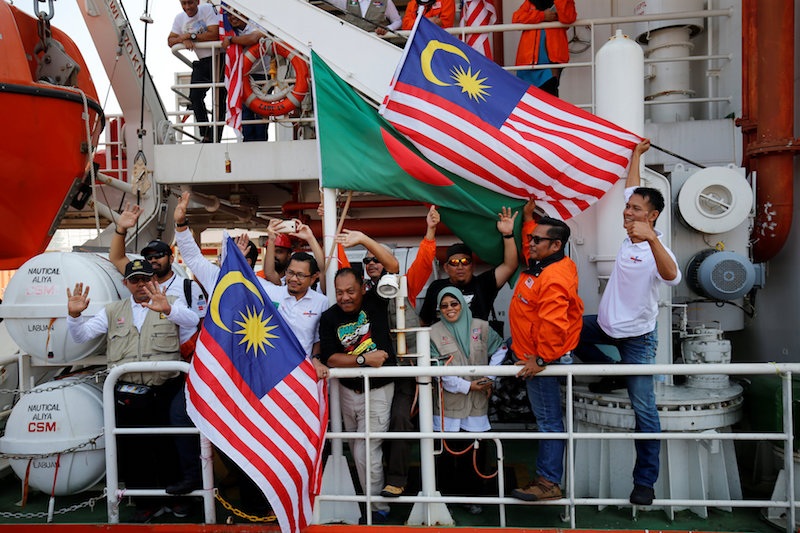 Volunteers of the Malaysian aid ship Nautical Aliya waving flags as they anchored to Chittagong Container Terminal with relief for Rohingya refugees in Chittagong February 14, 2017. — Reuters pic