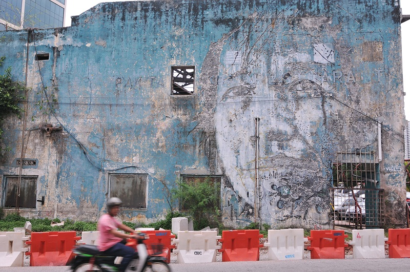A portrait of a woman drilled into the side of a vacant building by Vhils.