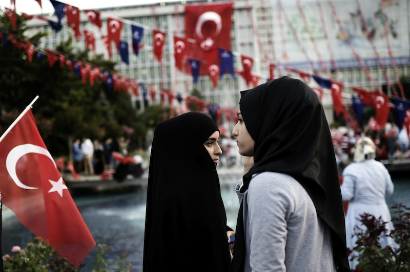This file photo taken on July 17, 2016 shows two young women in headscarves attending a pro-government demonstration outside the city hall in Istanbul. — AFP pic