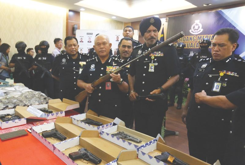Datuk Seri Mohmad Salled holds the seized rifle. Second from right is city police chief Datuk Amar Singh. ― Malay Mail pic