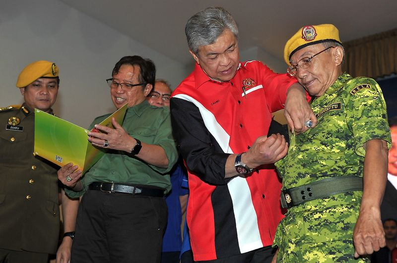 Deputy Prime Minister Datuk Seri Dr Ahmad Zahid Hamidi pinning the rank of Rela superintendent on London Tasin, 74, during a gathering with Rela member in a community hall in Lundu, February 12, 2017. Also present is Chief Minister Datuk Amar Abang Johari (left). — Bernama pic