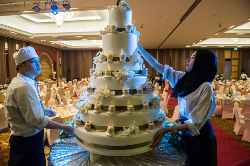 In this photograph taken on January 15, 2017, pastry chefs adorn a wedding cake before a wedding reception at the Al Meroz hotel in Bangkok. — AFP pic