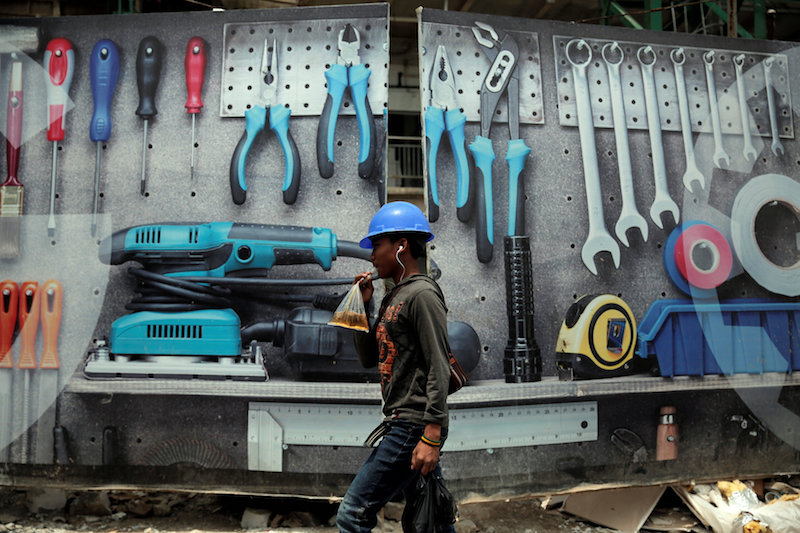 A worker drinks tea as he walks near a billboard of the construction of a new trade centre in Jakarta March 19, 2017. — Reuters pic