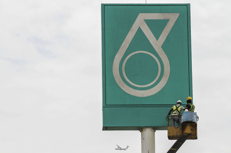 Workers work on a signage bearing the Petronas logo in Kuala Lumpur March 12, 2017. — Picture by Yusof Mat Isa
