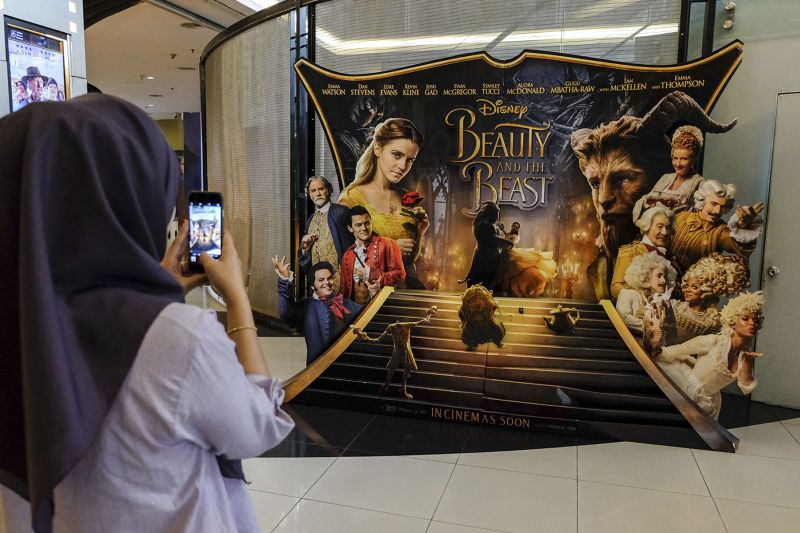 A woman takes a picture of the 'Beauty and the Beast' poster displayed at a cinema in Kuala Lumpur March 16, 2017. ― Picture by Yusof Mat Isa