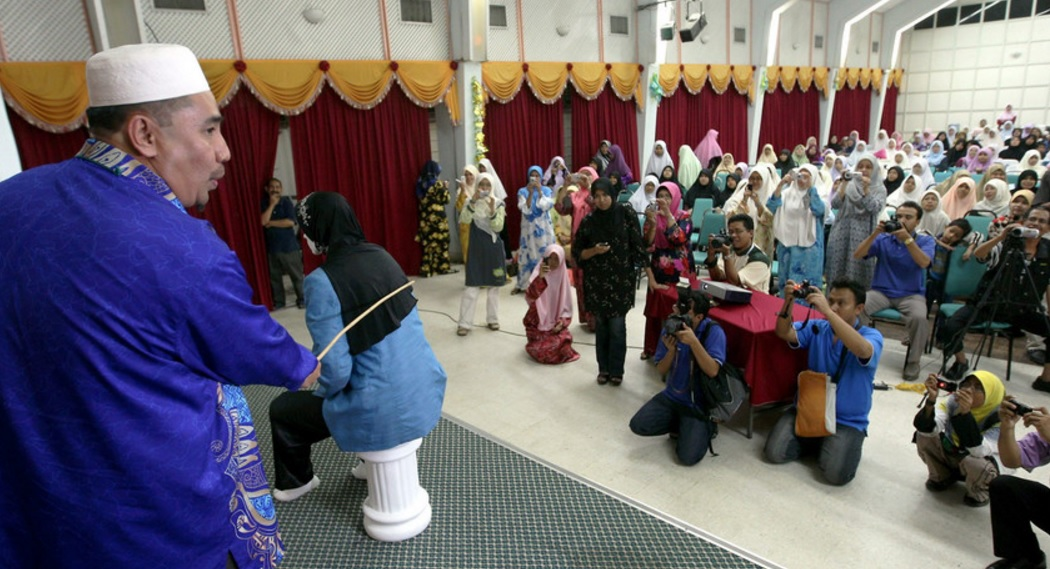 File picture of a public caning. Two women were punished by six strokes of the cane individually after they were found guilty of committing lesbian sex. — Bernama pic