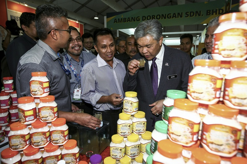 Datuk Seri Ahmad Zahid Hamidi (right) tries some locally made ginger honey during his visit to the Malaysia International Halal Showcase 2017 in Kuala Lumpur. — Reuters pic