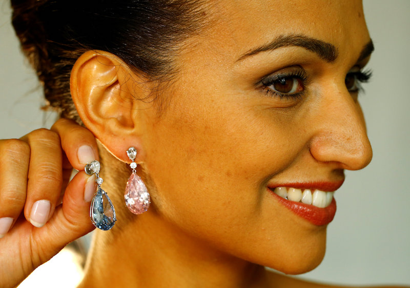 A model poses with the Apollo Blue and the Artemis Pink diamonds mounted as earrings during a preview for Sotheby's auction house in Geneva May 11, 2017.