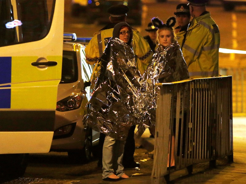 Two women wrapped in thermal blankets stand near the Manchester Arena, where US singer Ariana Grande had been performing, in Manchester, May 23, 2017. — Reuters pic