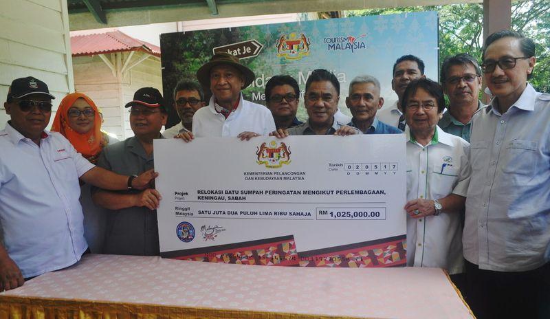 Datuk Seri Mohamed Nazri Abdul Aziz presents a mock cheque to Keningau District Officer Yusof Osman (seventh left), witnessed by Sabah Deputy Chief Minister Tan Sri Joseph Pairin Kitingan (left), May 2, 2017 in Keningau. — Bernama pic