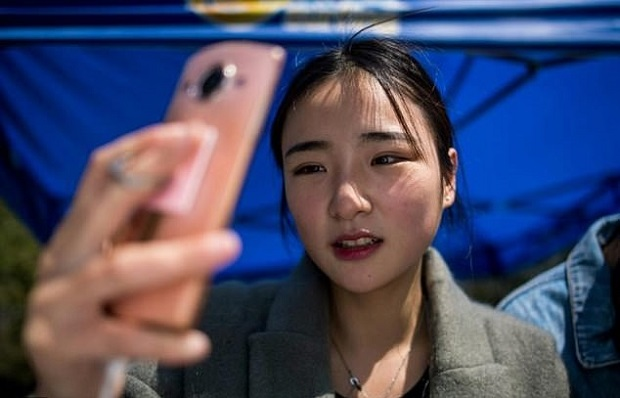 This picture taken on March 14, 2017 shows Jiang Mengna live broadcasting during a break at the Yiwu Industrial & Commercial College in Yiwu, east China's Zhejiang Province. — AFP pix