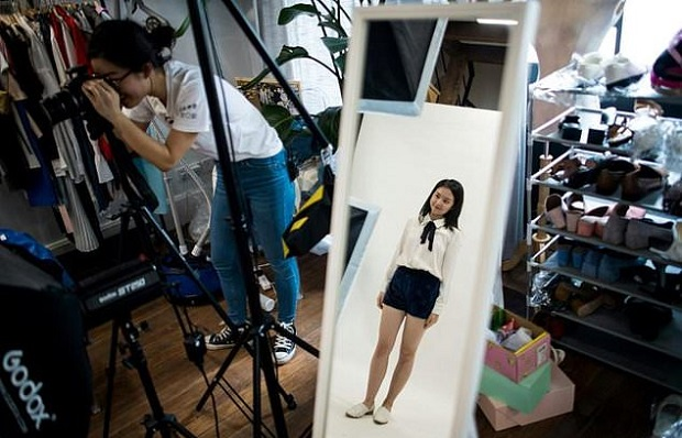 """This picture taken on May 5, 2017 shows Wang Houhou (left) taking pictures of a model for the website of her e-commerce startup """"gogoand"""" in Shanghai."""