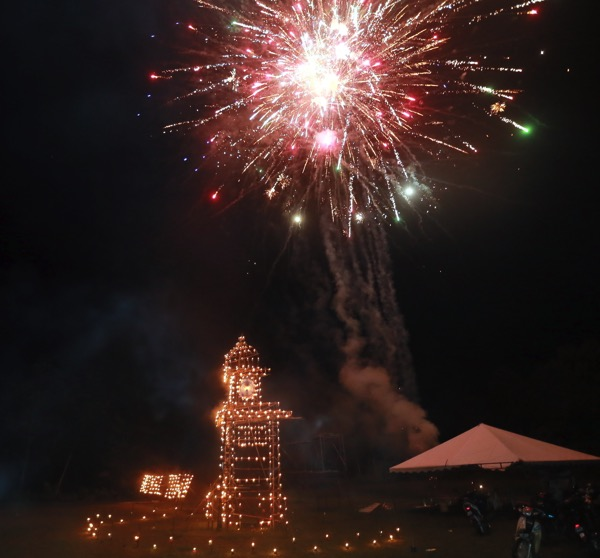 Fireworks light up the skies over a 'panjut' depicting a clock tower.