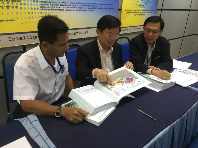State exco Chow Kon Yeow (centre) looks through the PSR EIA Report that is now on public display in Komtar. ― Picture by Opalyn Mok