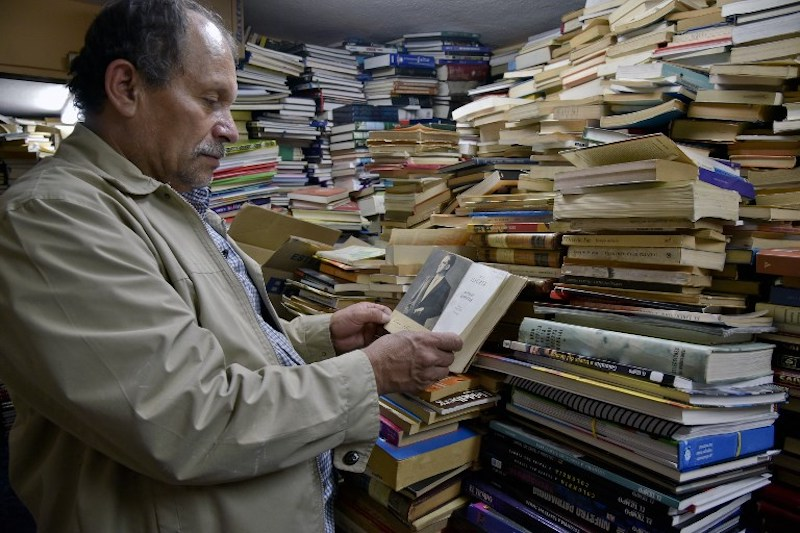 Jose Alberto Gutierrez checks books stacked in his library on the first floor of his house in Bogota May 18, 2017. — AFP pic
