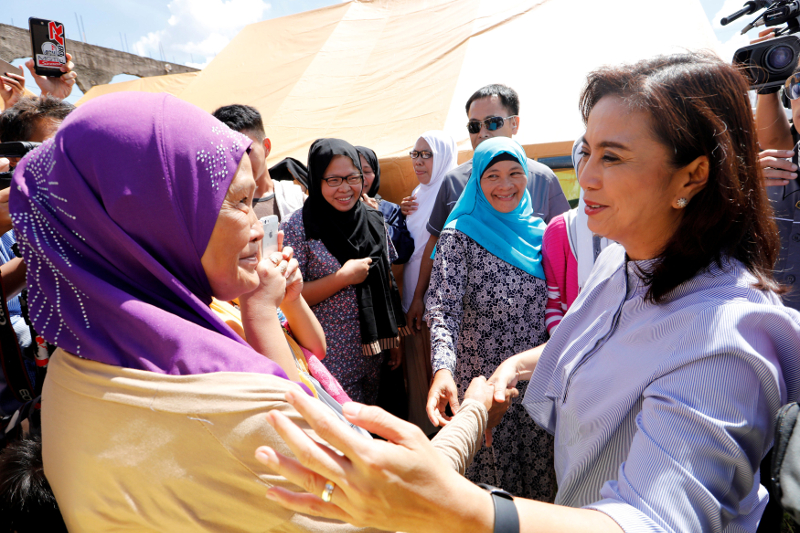 Leni Robredo (right) greets evacuated families at an evacuation centre outside Marawi with government forces still fighting insurgents from the Maute group in Marawi June 26, 2017. — Reuters pic